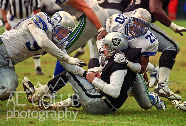 Oakland Raiders vs. Seattle Seahawks at Oakland Alameda County Coliseum Sunday, December 14, 1997.  Seahawks beat Raiders  22-21.  Seattle Seahawks defensive end Matt LaBounty (99) and defensive back Jay Bellamy (20) sack Oakland Raiders quarterback Jeff George (3).