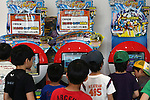 """May 9, 2010 - Tokyo, Japan - Young Japanese boys look at games on display in the official Pokemon store in Tokyo on May 9, 2010. Nintendo recently announced that the DS handheld device had become the best selling gaming handheld of all time, with a total of 129 million units sold. The DS 'family' have surpassed the """"Game Boy"""" series which hit 118 million over two decades."""