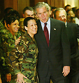 United States President George W. Bush poses for a photograph with Sergeant 1st Class Pearl Houck as Secretary of Defense Donald Rumsfeld (R) looks on during a visit at the Pentagon March 25, 2003 in Arlington, Virginia. Bush asked Congress for a wartime supplemental appropriations of $74.7 billion to fund needs directly arising from the war in Iraq and the global war against terror.   <br /> Credit: Alex Wong / Pool via CNP