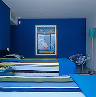 A Bertoia chair stands in the corner of this vibrant blue boy's bedroom