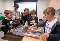 NWA Democrat-Gazette/BEN GOFF @NWABENGOFF<br /> Meg Benedetti, Scott Family Amazeum camp coordinator, gives feedback as campers Mykhael (CQ) Stone (from left), 7, Henry Woods, 10, Austin Schutz, 7, and Grayson Parrish, 8, modify Hot Wheels cars to float Wednesday, March, 21, 2018, during the &quot;Wheels, Wings &amp; Motorized Things&quot; Spring Break camp at the Scott Family Amazeum in Bentonville. The camp, inspired by the museum's temporary exhibit Hot Wheels: Race to Win, gives campers hands on opportunities to explore elements of physics such as gravity, friction and momentum.