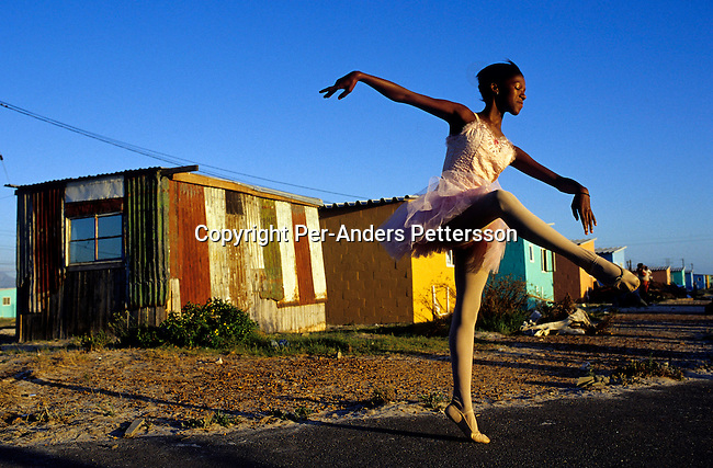 DIDANCE00150.Dance, Noluyanda Mqutwana strikes a pose outside her small family house on January 30, 2000 in Khayelitsha, the biggest black township, about 20 miles outside Cape Town, South Africa. Noluyanda dances ballet in a school called 'Dance For All', which teaches unprivileged children dance after school. Many children are talented and the discipline taught during the dance classes has helped many to improve their concentration in school. .©Per-Anders Pettersson/iAfrika Photos