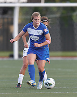 Under pressure, Boston Breakers forward Katie Schoepfer (12) passes the ball.  In a National Women's Soccer League Elite (NWSL) match, the Boston Breakers (blue) tied Western New York Flash (white), 2-2, at Dilboy Stadium on June 5, 2013.