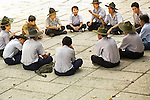 Boy Scouts of Vietnam sit on floor of temple in circle with leaders talking