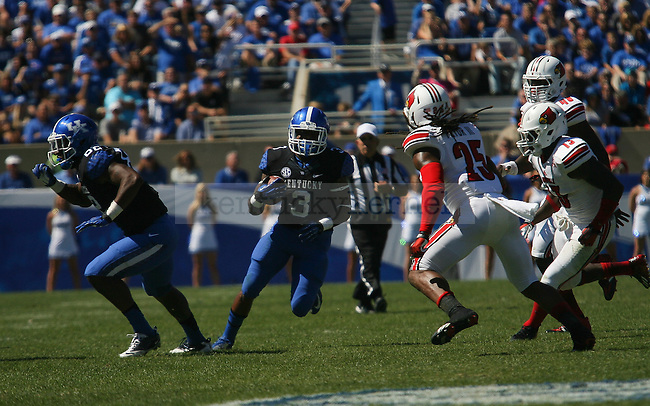Freshman running back Jojo Kemp runs through a hole in the UofL defense in Lexington, Ky., on Saturday, September 14, 2013. Photo by Michael Reaves   Staff