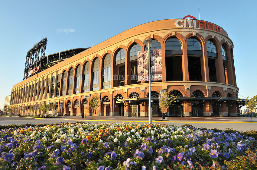 Panoramic view of Citi Field, Home of the Mets, Flushing, Queens, New York City. Southwest elevation as a brilliant sun sets. No game day, empty parking lot, flower bed foreground.