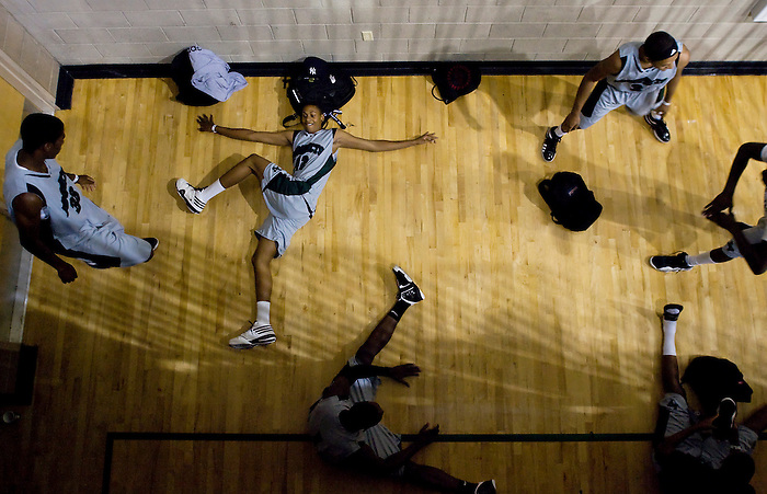 Members of the Las Vegas Prospects basketball team stretchs behind the bleachers at Rancho High School in Las Vegas, Nev., Thursday, July 23, 2009 before the start of a game at the Adidas Super 64 tournament.