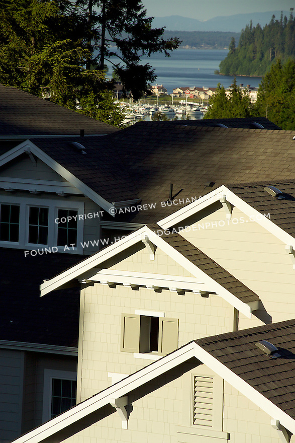 Bright late afternoon sunshine spills acrosss the second story, shingled facade, asphalt shingle roofs, and white trim painted dormers and rooflines of a contemporary new home in a resort development, seen with the water, mountains, tall evergreen trees, and more houses in focus in the not-too-distant background.
