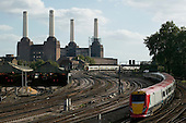 Train on railtrack leading to Victoria Station in London with iconic building of Battersea Power Station in the background.