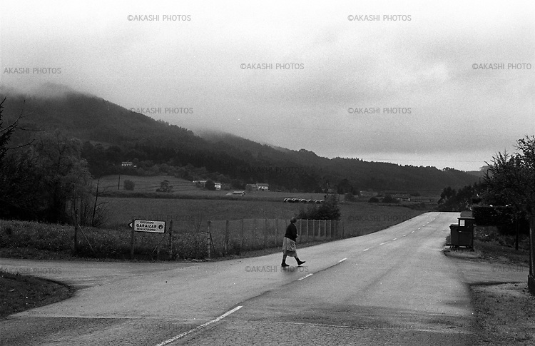 April 17, 2005. An old woman crosses a road after a rain in Maruri, Spain..(Photo by Toru Morimoto)