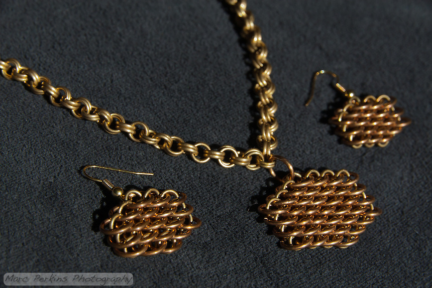 "A completed maille earring and necklace set that Michelle has titled ""Honeyscale"", as it makes her think of honey and bees.  The necklace is a simple double cable (4-in-2) weave made out of 19 gauge 5/32"" ID brass.  The earrings and pendant are both dragonscale weave made out of 18 gauge 1/4"" ID bronze and 19 gauge 5/32"" ID brass."