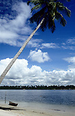 Pernambuco, Brazil. Beach with white sand and two people swimming and a small boat with a plantation across the lagoon.