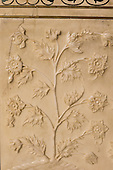 Agra, Utar Pradesh, India. Detail of floral relief carving in marble on the Taj Mahal, depicting a flowering plant, with semi-precious stole inlay work above.