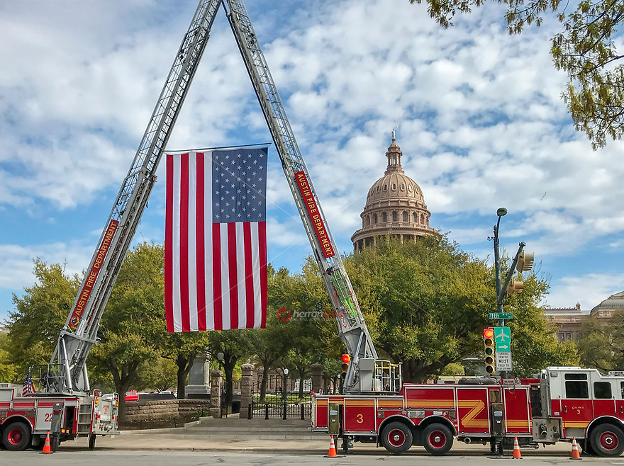 """A wonderful site to see """"old glory"""" US flag display by cranes on the Austin Fire Department fire engines in front of the Texas State Capitol."""