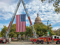 "A wonderful site to see ""old glory"" US flag display by cranes on the Austin Fire Department fire engines in front of the Texas State Capitol."