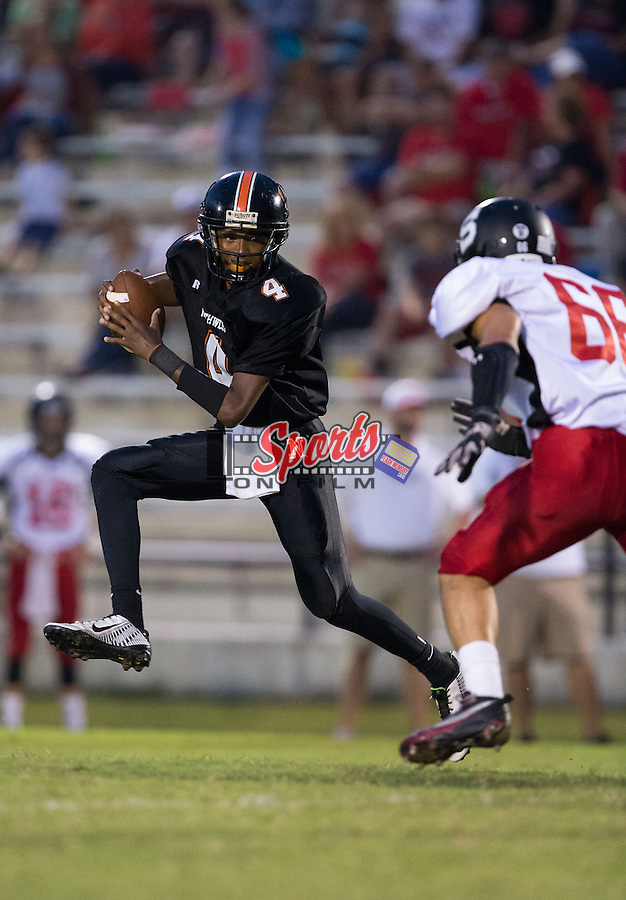 Northwest Cabarrus Trojans quarterback Kalan Chapman (4) tries to avoid the pursuit of Grex Urey (66) of the South Rowan Raiders during first quarter action at Trojan Stadium September 12, 2014, in Concord, North Carolina.  (Brian Westerholt/Sports On Film)