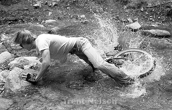 Alex Van Valin mountain biking through a stream.<br />