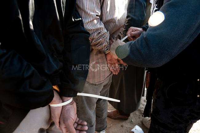 KIRKUK, IRAQ: A policeman handcuffs suspects with zip ties during an anti-terror raid...Kirkuk, the oil-rich city in northern Iraq, is home to Kurds, Arabs, Turkomen, Christians, Kakayi, and numerous other ethnicities. Since 2003, thousands of its residents have been killed or injured in terrorist attacks...As the US military leaves Iraq, the future of this violent and ethnically diverse city remains unsure...Photo by Pazhar Mohammad/Metrography