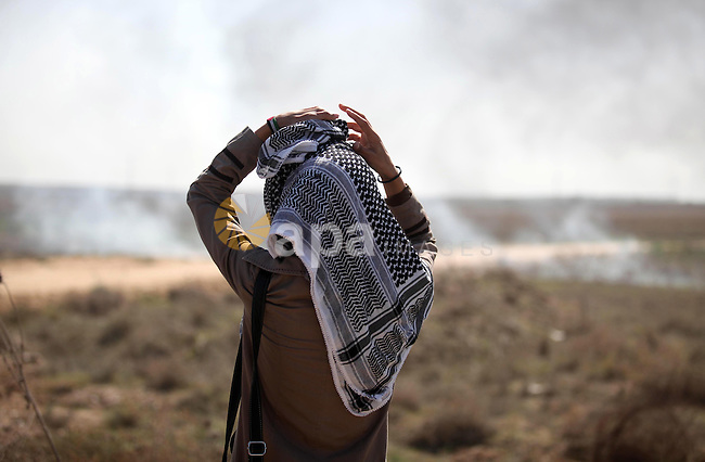 """A female Palestinian protester looks on during clashes with Israeli security forces near the border fence between Israel and the Gaza Strip on October 11, 2015, east of Gaza City. An Israeli air strike in Gaza killed a pregnant woman and her toddler and Hamas warned the Jewish state against """"foolishness"""" as Palestinian unrest spun further toward a full-scale uprising. Photo by Ashraf Amra"""