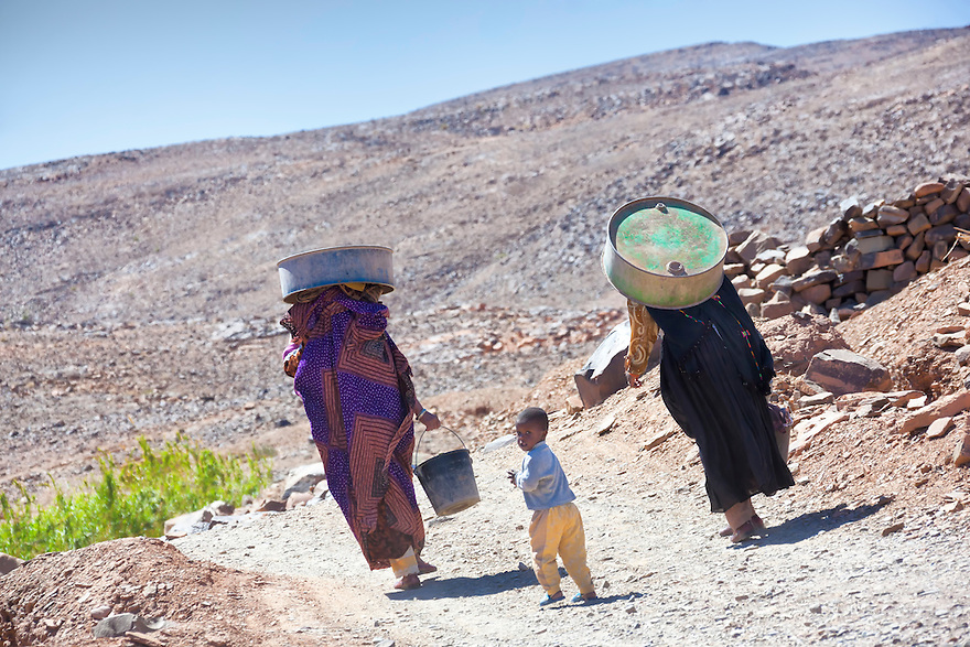 Two moroccan women with child on their way home from washing cloths in the river.