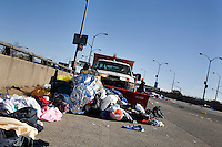 A truck gathers discarded clothing and other trash as volunteers and independent contractors help gather clothing and trash littering the on-ramp to the Verrazano-Narrows Bridge after the start of the ING New York City Marathon on Staten Island on 07 November 2010.