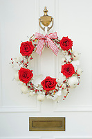 A Christmas wreath made of red roses, red berries and small white apples adorns the front door