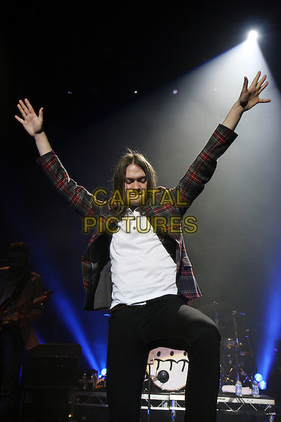 KASABIAN -Tom Meighan .Performing live at the R.A.Hall as part of the concerts in aid of Tennage Cancer Trust, Royal Albert Hall, London, England..March 27th, 2009.stage concert gig music band half length 3/4 arms in air white top jeans denim black red tartan plaid jacket grey gray .CAP/MAR.© Martin Harris/Capital Pictures.