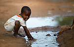 A boy plays in a water puddle in a camp in Mopti, Mali, for families displaced by the fighting in the north of the country. Islamist rebels seized control of the north of Mali in 2012, but were chased out in early 2013 by French troops. Many displaced and refugee families have yet to return, preferring to wait for better security and improved economic conditions in the north.
