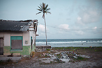 A tumb in front of a house in Annibare. A young boy was buried there, after drowning in a water tank. Land is restricted in Nauru, due to extensive mining inland. Cemetery are full, so some Nauruans have been allowed to bury their family member in front of their house...Nauru, officially the Republic of Nauru is an island nation in Micronesia in the South Pacific.  Nauru was declared independent in 1968 and it is the world's smallest independent republic, covering just 21 square kilometers..Nauru is a phosphate rock island and its economy depends almost entirely on the phosphate deposits that originate from the droppings of sea birds. Following its exploitation it briefly boasted the highest per-capita income enjoyed by any sovereign state in the world during the late 1960s and early 1970s..In the 1990s, when the phosphate reserves were partly exhausted the government resorted to unusual measures. Nauru briefly became a tax haven and illegal money laundering centre. From 2001 to 2008, it accepted aid from the Australian government in exchange for housing a Nauru detention centre, with refugees from various countries including Afghanistan and Iraq..Most necessities are imported on the island..Nauru has parliamentary system of government. It had 17 changes of administration between 1989 and 2003. In December 2007, former weight lifting medallist Marcus Stephen became the President.