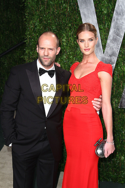 Jason Statham & Rosie Huntington-Whiteley.2012 Vanity Fair Oscar Party hosted by Graydon Carter held at the Sunset Tower, West Hollywood, California, USA..February 26th, 2012.half length black tuxedo red dress couple silver clutch bag.CAP/ADM/SLP/RU.©Ryan Upling/SLP/AdMedia/AdMedia/Capital Pictures.