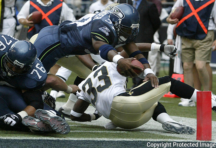 Seahawks' running back Shaun Alexander dives past Saint's cornerback Ashley Ambrose and into the end zone to score his second touchdown of the first half half on Sunday, Sept. 7, 2003 at Seahawks' Stadium. (AP Photo/Jim Bryant)