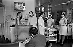NHS 1970s Uk, doctors Ward Round at Charing Cross Hospital London. Patients allowed to wander around within the ward, eat their meals and watch television 1972.<br /> The meal trolley is being pushed around by one of the junior nurses, you can see her watch and name tag on her white uniform. It looks like she is clearing away  the first course, salt and pepper shakers are on the middle shelf. On the top of the trolley there is the puddings - second course, in small  rectangular dishes. On the shelf below the TV there is a model aeroplane and galleon boat, no-doubt made by patients.