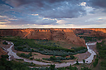 "A flooded Chinle Wash creates a ""horseshoe bend"" around the De Chelly sandstone walls as seen from Tsegi Overlook at sunset"
