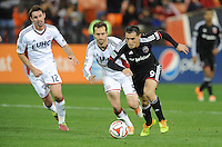 Washington, D.C.- March 29, 2014. Fabian Espindola (9) of D.C. United runs with the ball from A.J. Soares (5) of the New England Revolution.  D.C. United defeated the New England Revolution 2-0 during a Major League Soccer Match for the 2014 season at RFK Stadium.