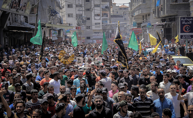 Mourners carry the body of Palestinian Mahmoud Al-walayda, one of three armed Palestinians killed overnight in Israeli fire along the border with the Gaza Strip, mourn during his funeral in Beit Lahya in northern Gaza strip on August 18, 2019. Israeli forces last night killed three Palestinians and injured a fourth one in an artillery attack near the town of Beit Lahia, north of the Gaza Strip, according to the Ministry of Health. Photo by Anas Elshareef