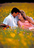 Lovers relax in field of coreopsis, wild flower field. Couples. romance, relaxation.