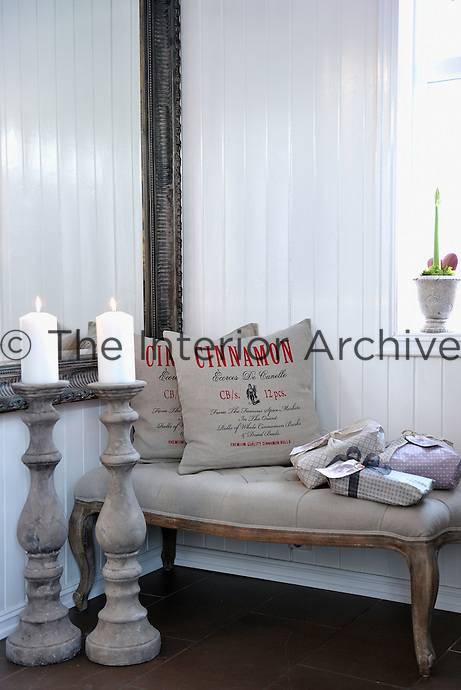 An antique bench, mirror and a pair of large candlesticks furnish this white-painted entrance hall