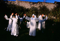 Novices studying to become nuns sing in the garden behind the walls of Santa Catalina Convent. The young cloistered nuns are allowed a break in their silence as they learn the strict life in a convent. Seven times during the day the nuns go to their chapel for chorus and pray. Contemplation is the most important thing in their lives and as well as study.<br /> <br /> Monasterio de Santa Catalina was built in 1580.  Of the 30 cloistered nuns, the youngest nun is 15 and the oldest is 98. They begin their day at Mass, then the novicias have class and activities studying theology, music and the Bible. For their work, they embroider, make parsley soap, creams, cookies and iron. Older nuns make  the wafers for communion. They never leave the premises unless they have special permission to go to the doctor and to vote. The founder was supposed to have accepted girls from the finest of Spanish families. The nuns today take the traditional vow of poverty.