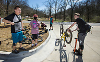 Cooper Heasley (right) of Little Flock chats with Chineng Yang of Saint Paul, Minn. Wednesday, March 11, 2020, while stopping to borrow a pump at the Northeast A Street trailhead on the Razorback Greenway in Bentonville. The Yang family said they make a annual trip to Northwest Arkansas to ride the mountain bike trails. Check out nwaonline.com/200312Daily/ for today's photo gallery<br /> (NWA Democrat-Gazette/Ben Goff)