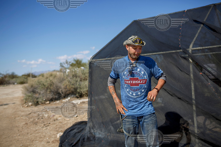 John, 27, from Louisiana where he was born and raised beside his tented home in Slab City, a squatters' camp about 190 miles southeast of Los Angeles. A veteran, John served in Afghanistan for two years. <br /> <br /> Slab City, known as The Slabs, is named for its areas of concrete where for many years, since the military based closed, people have parked their RVs as they travel south for the winter. There is also a permanent community of 'Slabbers', around 200 people, who have established themselves living free in the Sonoran Desert where temperatures can reach 48 Celsius in the summer and, while there is no rent, there is also no water, electricity or services. Slabbers are an eclectic bunch often escaping poverty but also holding in common the desire to escape the rules and order of society in what they like to call 'the last free place on earth'.