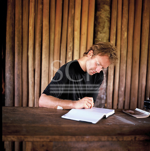 Pavuru village, Brazil. Sting writing at a table in an Indian house; Xingu Indigenous area, Brazil; Nov 1990.