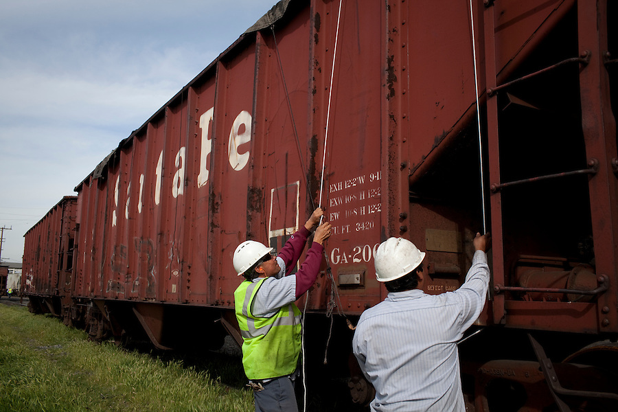 Los Angeles, California, March 1, 2010 - Workers use straps to tie down open freight cars at the Los Angeles Harbor Grain Terminal. A decline in U.S. consumption has left exports short of a good exit strategy. In 2009, imports fell 28%. This has created a bottleneck for exports, which need the shipping containers to move product overseas. ..