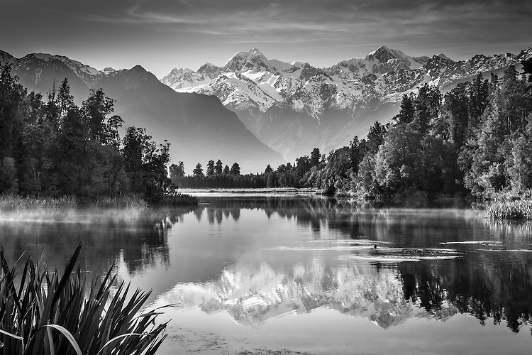 Misty morning and perfect reflections of Mt Cook, Mt Tasman & Southern Alps at Lake Matheson, Westland Tai Poutini National Park New Zealand.
