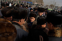 Uighur men bargain for used mobile phones in Kashgar, Xinjiang, China.
