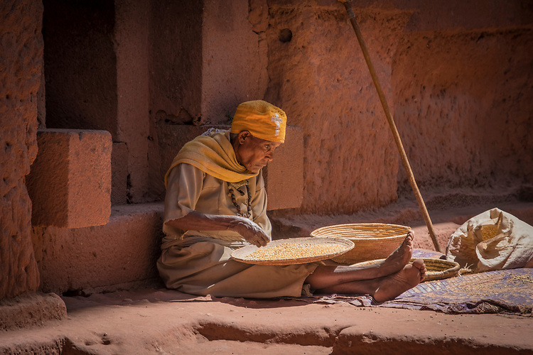 An elderly man carefully removes chaff from grain in the outer courtyard at one of Lalibela's rock-hewn churches.