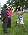 Keith Lopez and ? reporter, seen at work outside the Suffolk County District Attorney Building in Hauppauge where a grand Jury was hearing testimony involving the Roman Catholic Church's handling of sex abuse complaints on Monday July 1, 2002. (Photo by Jim Peppler).