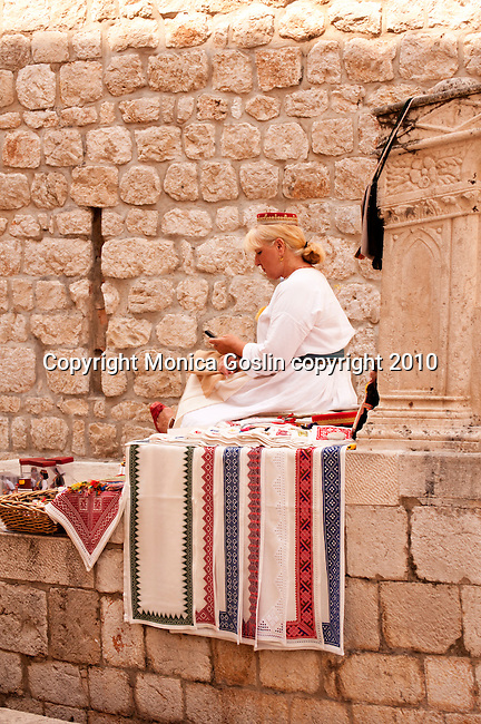 A woman dressed in traditional clothing sits on the stone steps leading up to the Dominican Monastery in Dubrovnik, Croatia and sews traditional patterns on cloth for table mats, table runners, and more.