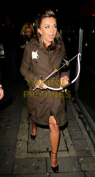 LOUISA LYTTON .At her 20th Birthday Party, Embassy Nightclub, Old Burlington Street, London, England, February 14th 2009..Valentine's Day full length brown trench coat bare legs black ankle strap shoes  cupid's bow and arrow toy prop funny .CAP/CAN.©Can Nguyen/Capital Pictures
