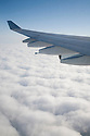 An airplane wing above clouds. The airplane is Airbus A340, operated by Cathay Pacific airline.