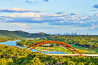 The Pennybacker Bridge with Lake Austin as the clouds hoover over the city  skyline in the background.  The Austin 360 bridge is an iconic view of austin with the scenic blue waters of the lake meandering toward the city with all the  greenery from the golf course and trees with the Austin cityscape.